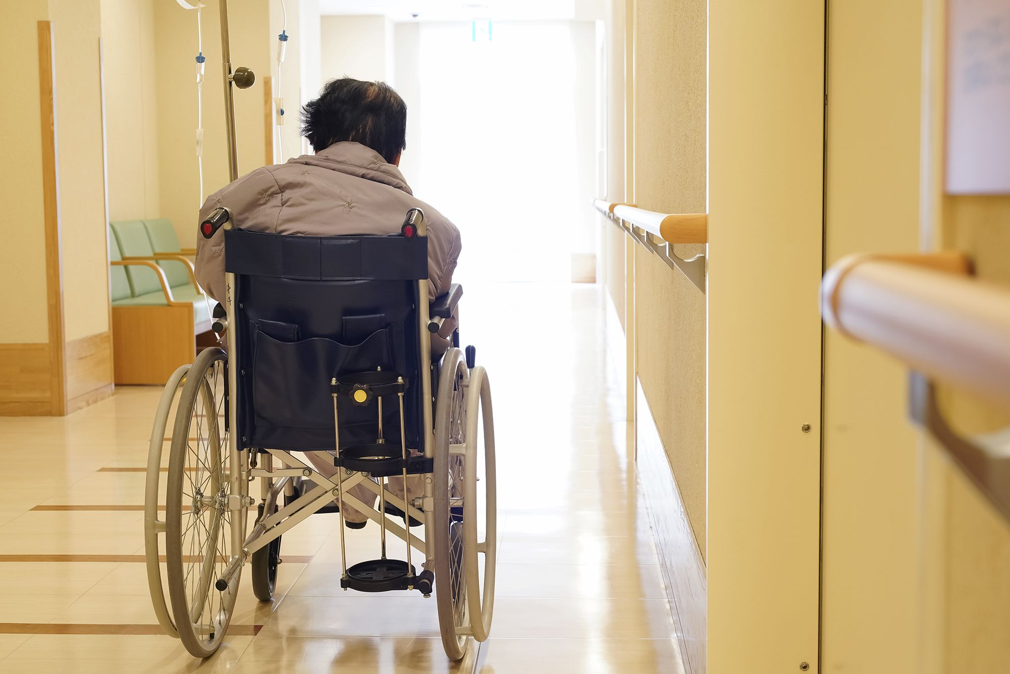 An elder woman in a wheelchair in a nursing home hallway