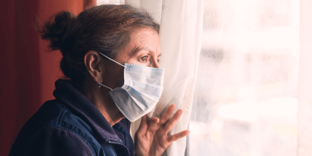 Nursing home resident wearing a covid19 mask looking out a window.